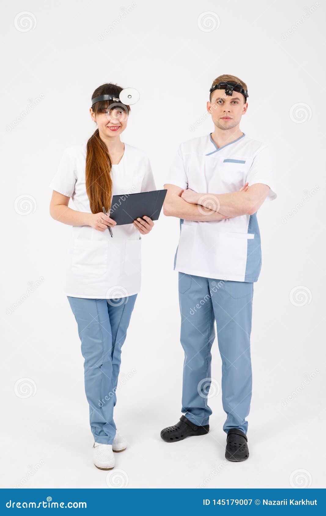 Personel medyczny Portret dwa otolaryngologists pracuje na odosobnionym bia?ym tle kt?ry rozwi?zuje r??norodnych zagadnienia
