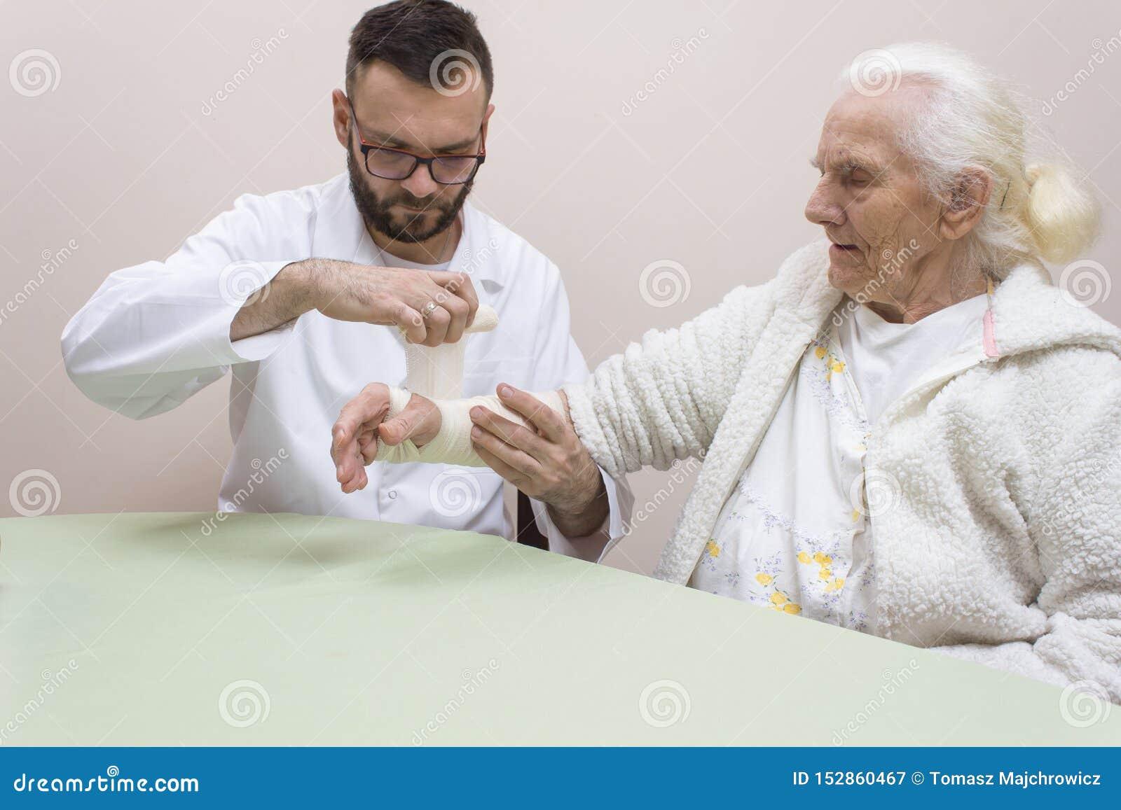Personen med paramedicinsk utbildning i ett vitt förkläde sätter på stänger och en dressing på handleden av en mycket gammal grå