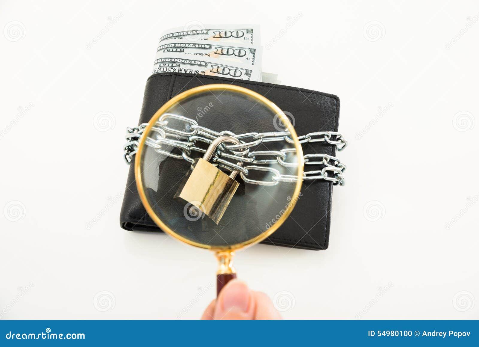 Personhand med förstoringsglaset över plånboken