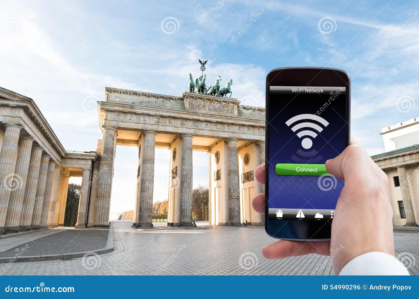 Personhand med mobiltelefonen på den brandenburg porten