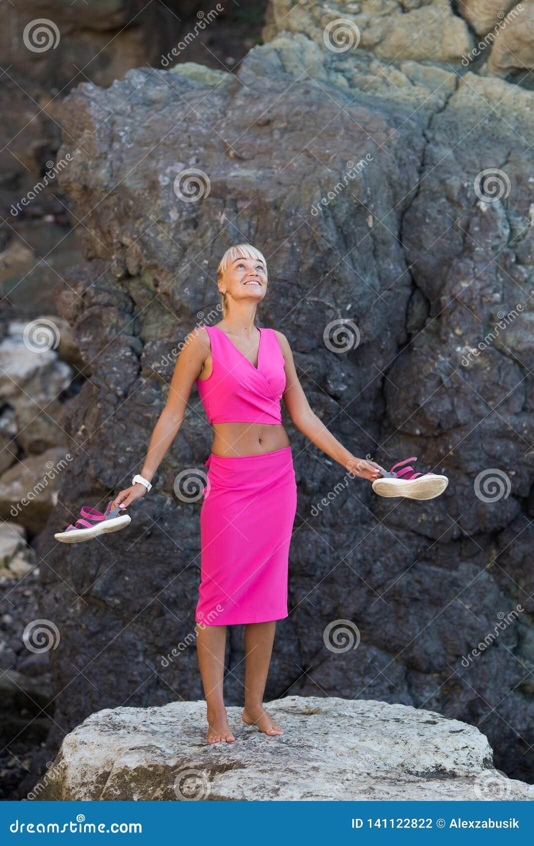 Personne féminine d une chevelure blonde bronzée se reposant à l endroit reculé du bord de la mer rocheux sauvage