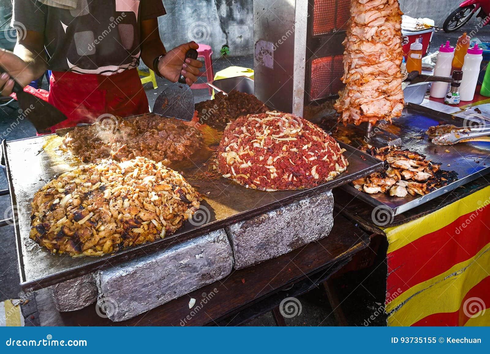 Personne grillant et viande de torréfaction pour le repas de pain pita de shawarma