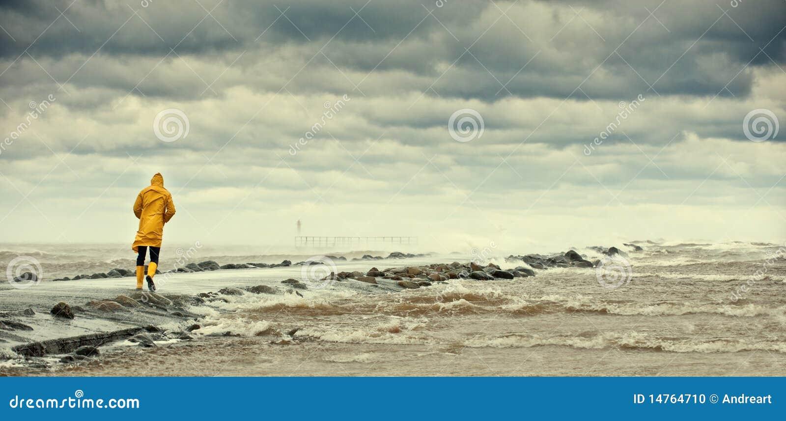 Personne marchant par la mer orageuse