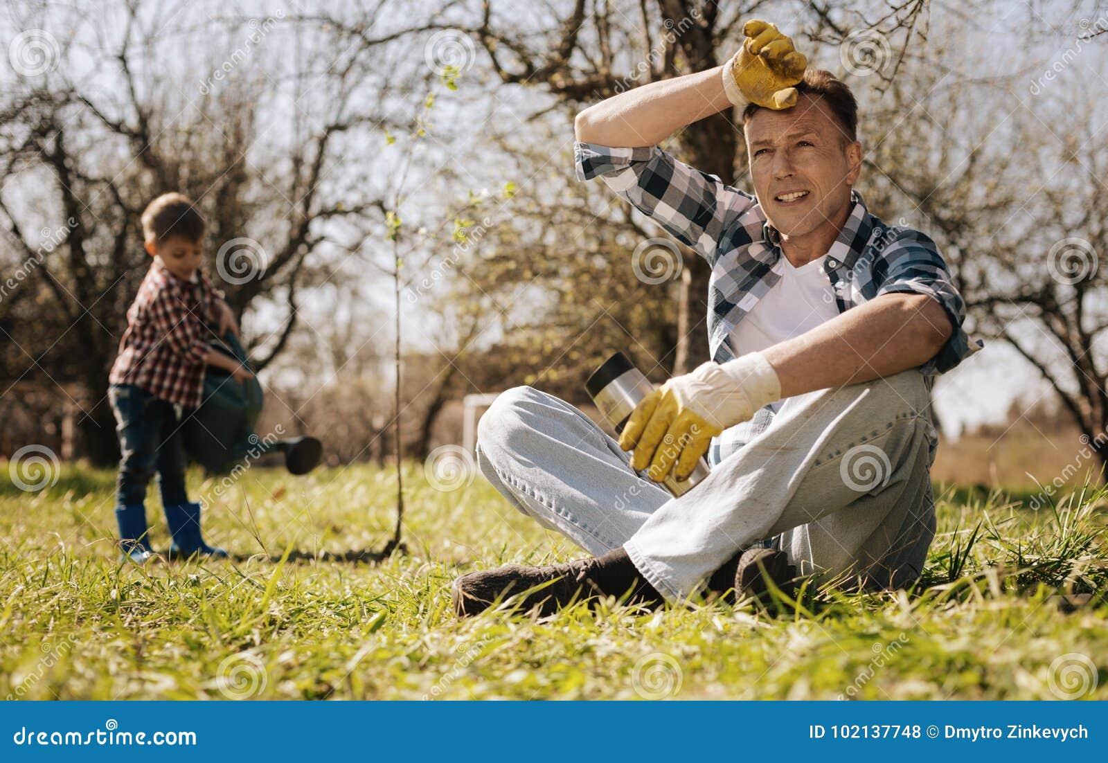 Personne masculine fatiguée tenant la thermo-tasse tout en ayant le repos sur l herbe