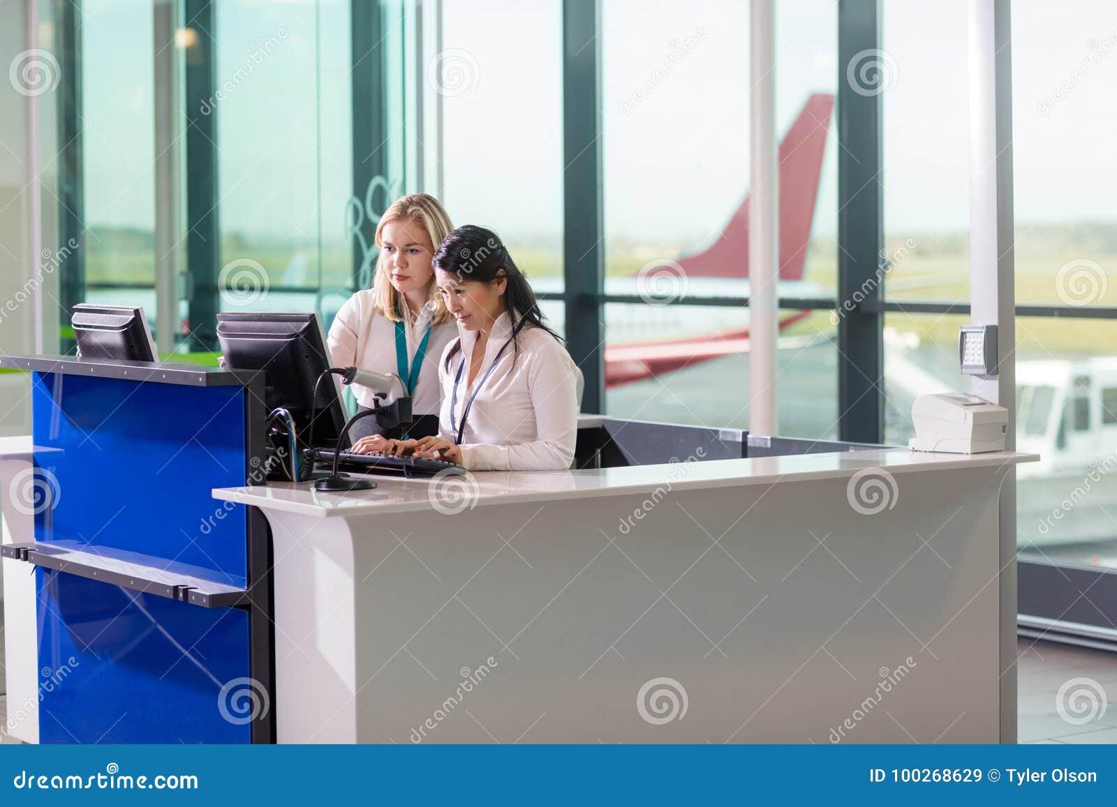Personnel au sol à l aide de l ordinateur au compteur dans l aéroport
