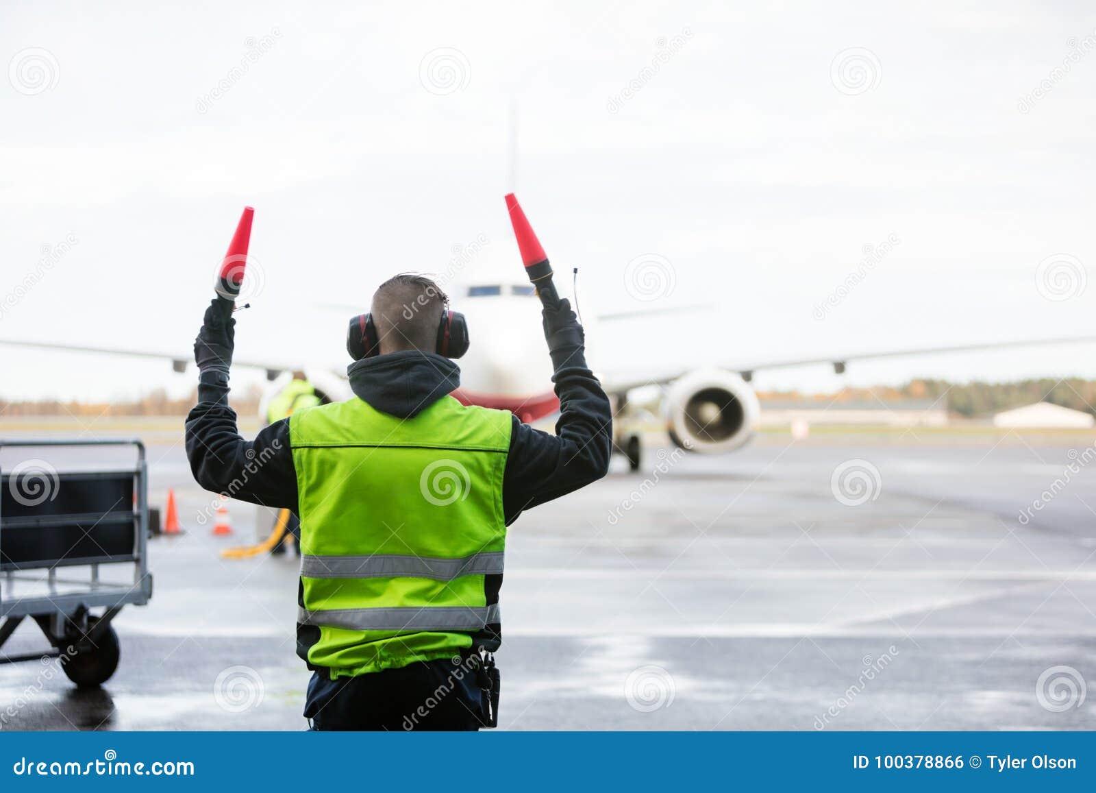 Personnel de piste signalant à l avion
