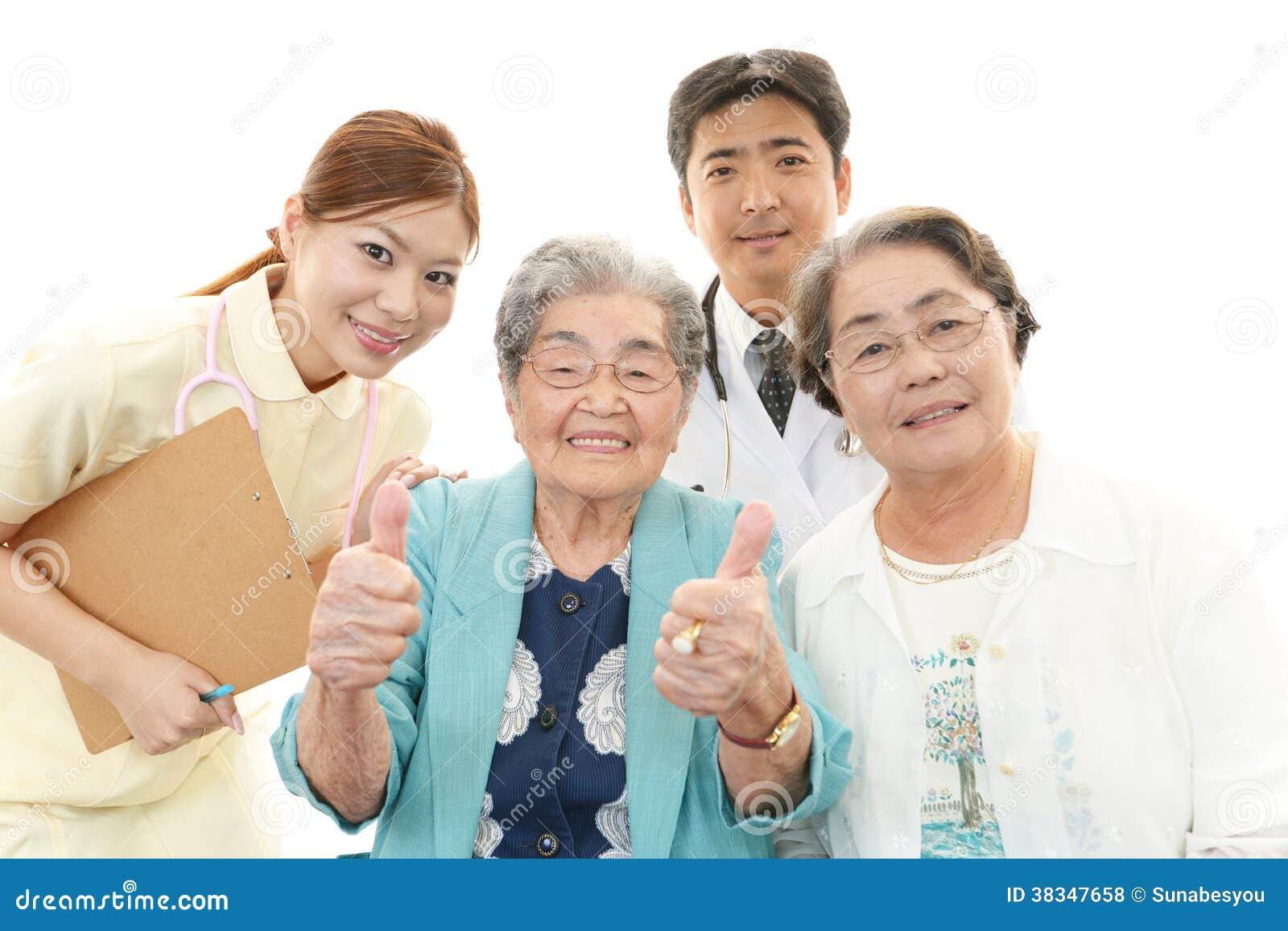 Personnel médical asiatique de sourire avec dames âgées