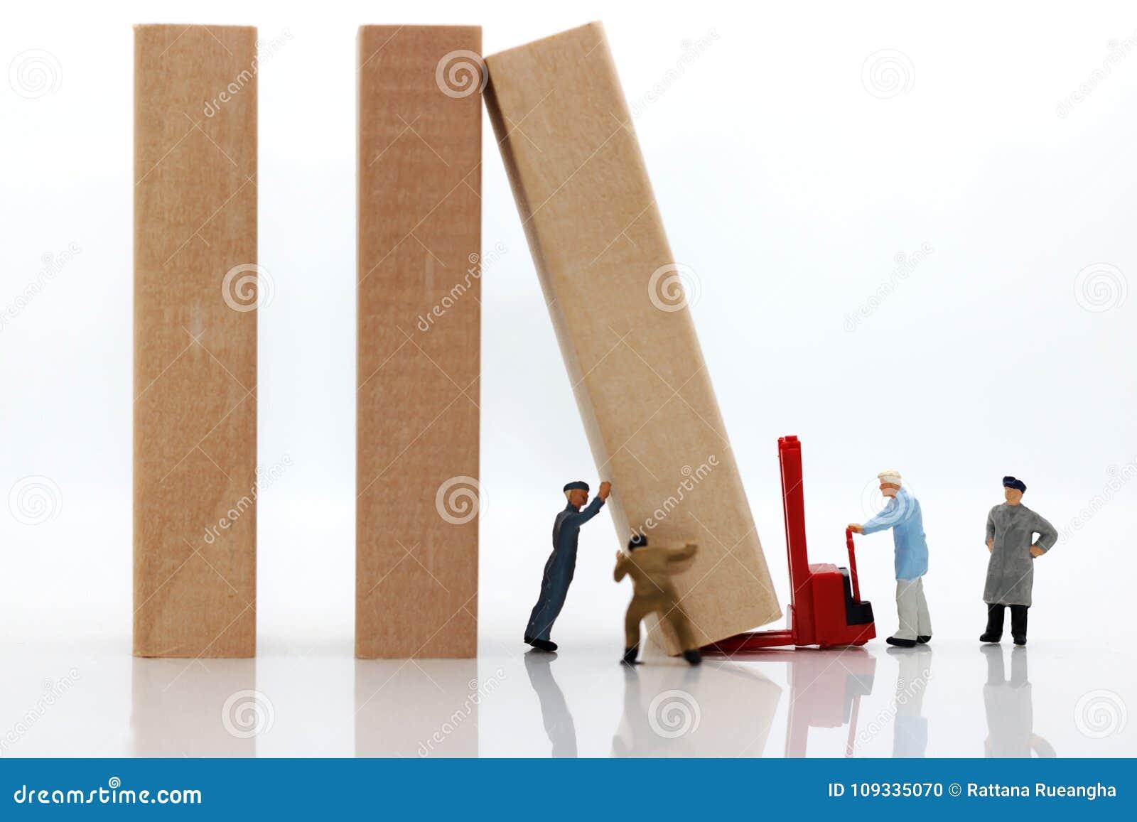 Personnes miniatures : Équipe de travailleurs arrêtant l effet de domino,