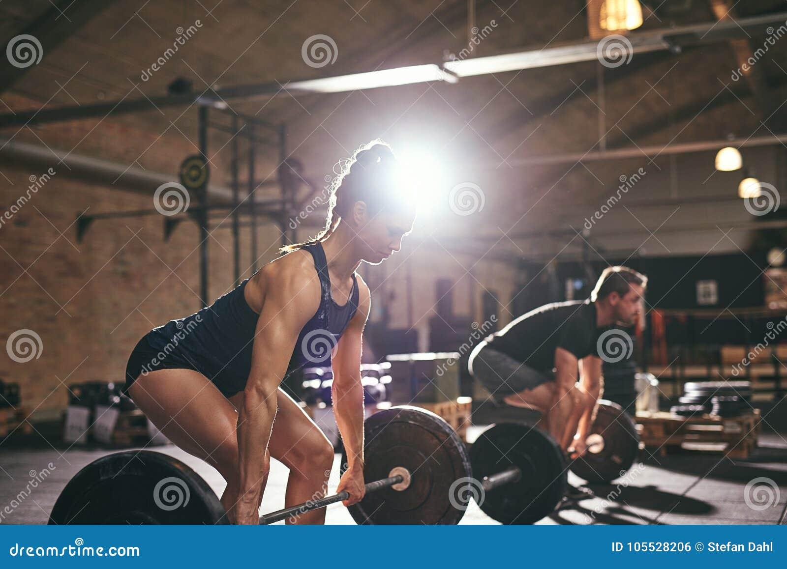 Personnes musculaires faisant l exercice avec le barbell lourd