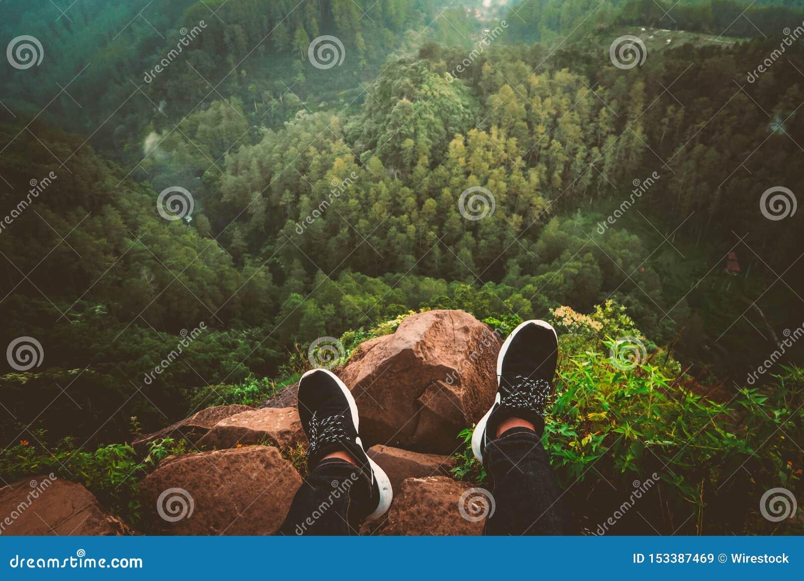 Persons fot i gymnastikskor som sitter på en stenig klippkant som ser en härlig skog och kullar