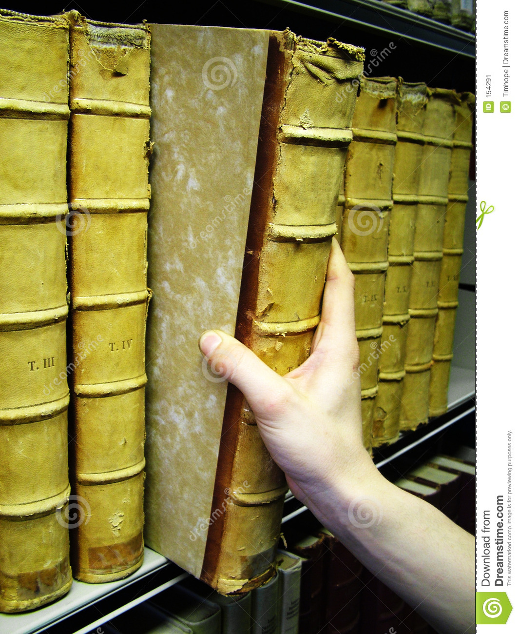 Persons hand removing old book from bookshelf