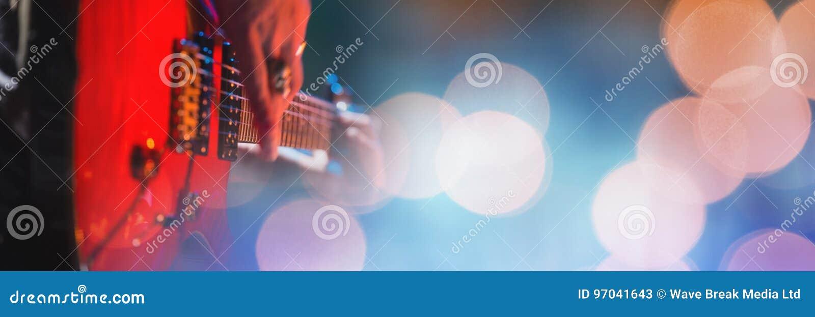 Persoon die elektrische gitaar met gele lichten spelen
