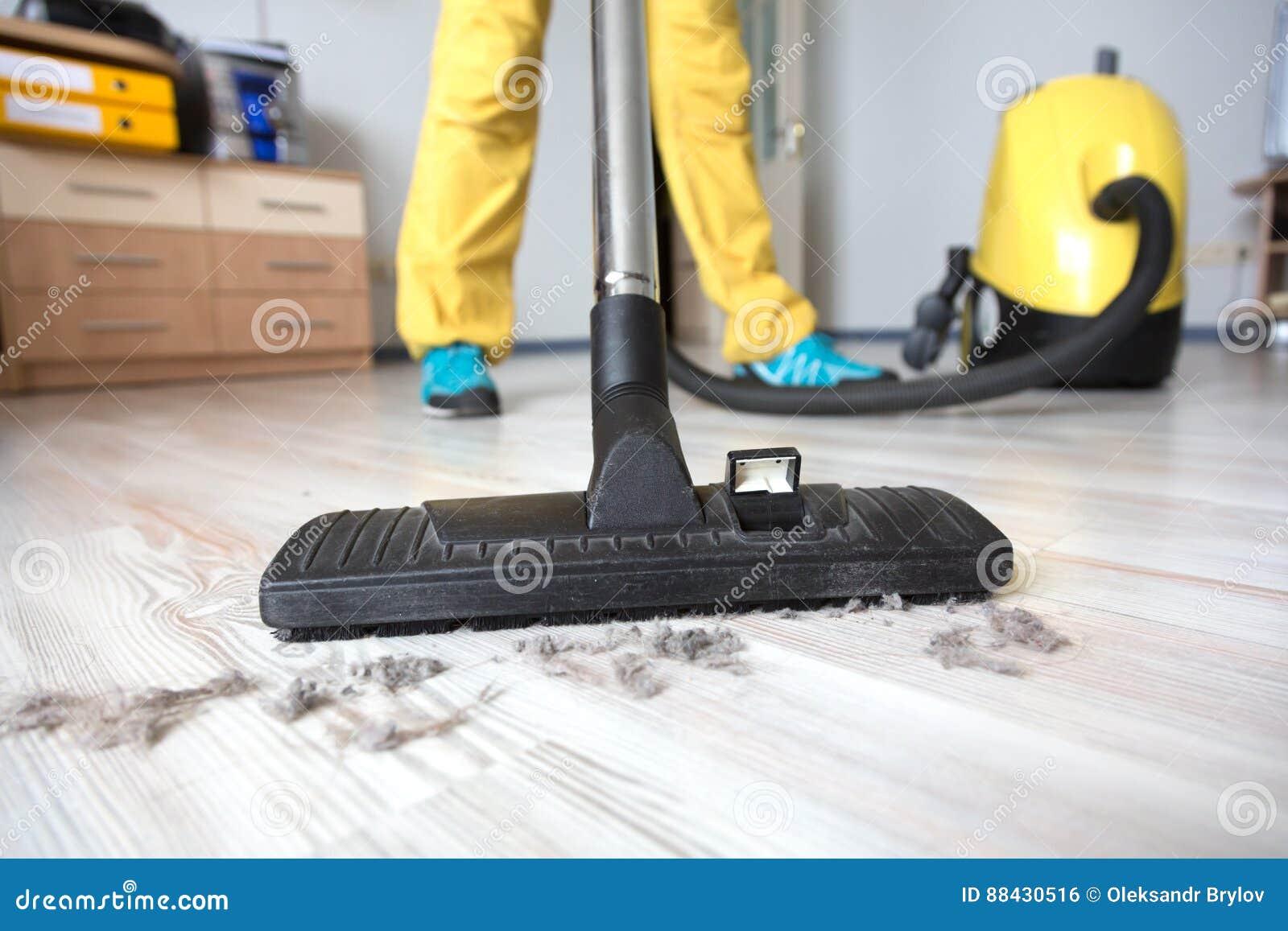 Persoon die houten vloer met stofzuiger schoonmaken stock foto