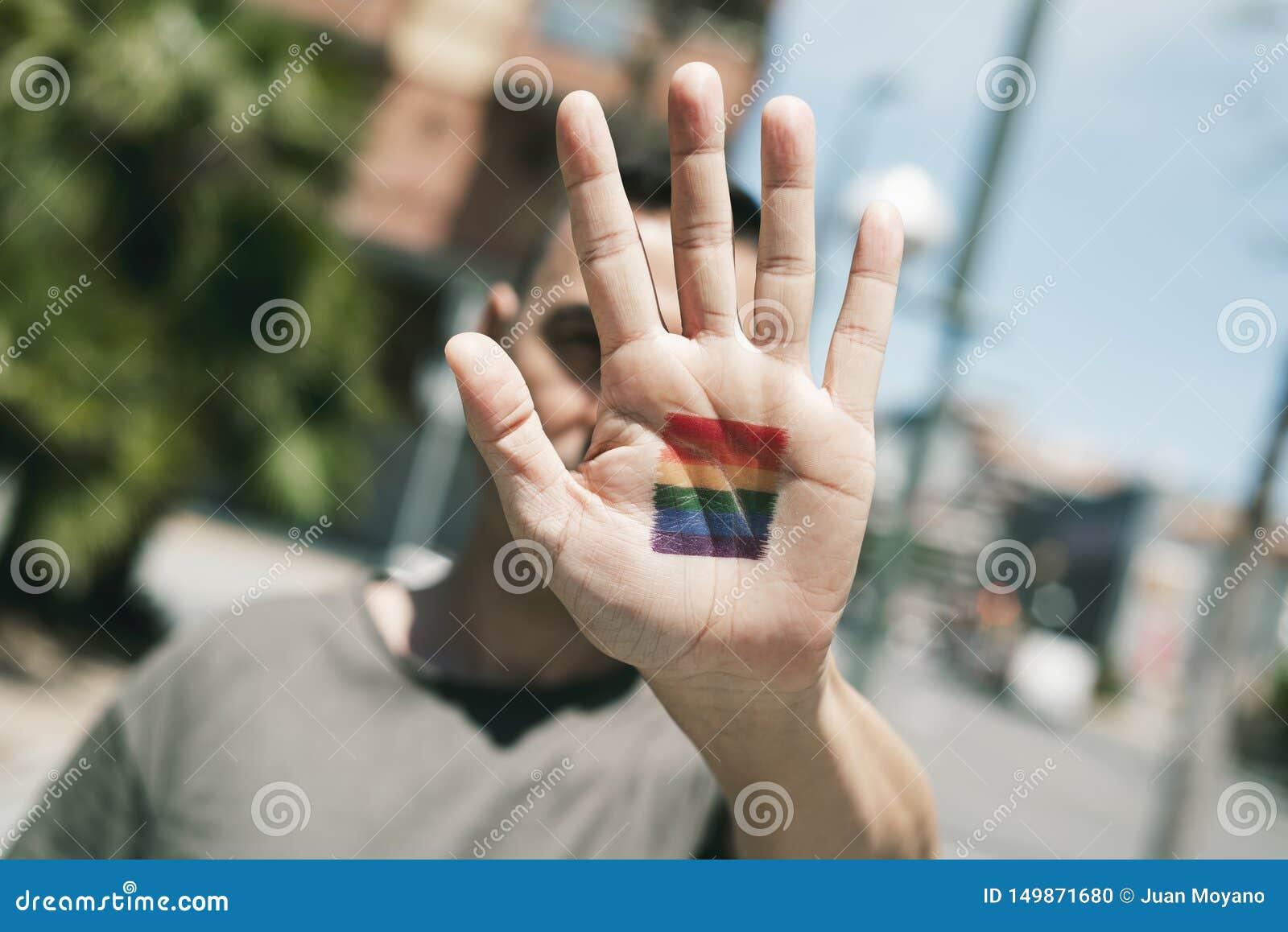 Persoon met een regenboogvlag in zijn of haar hand