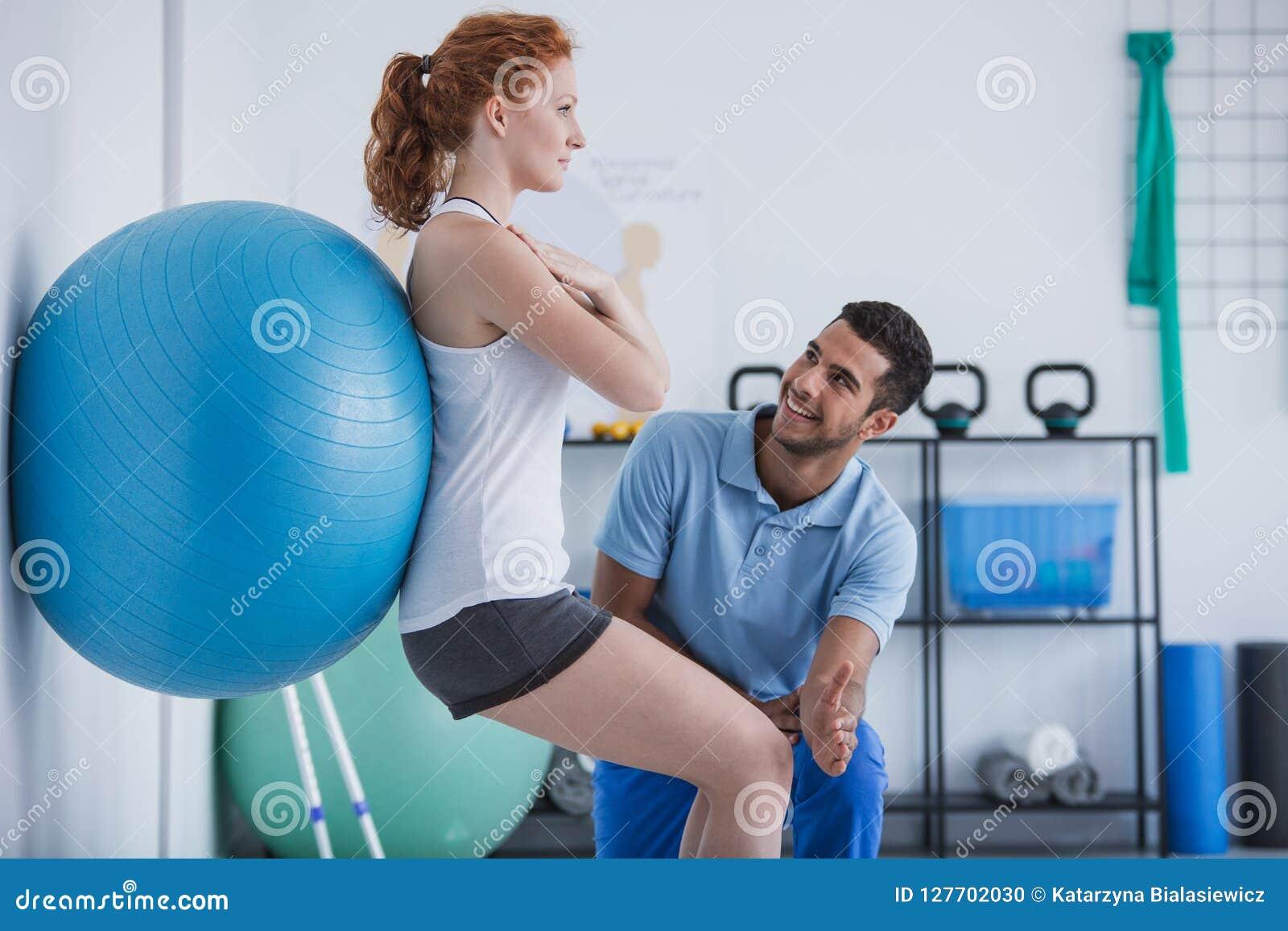 Persoonlijke trainer die sportvrouw helpen die met bal uitoefenen