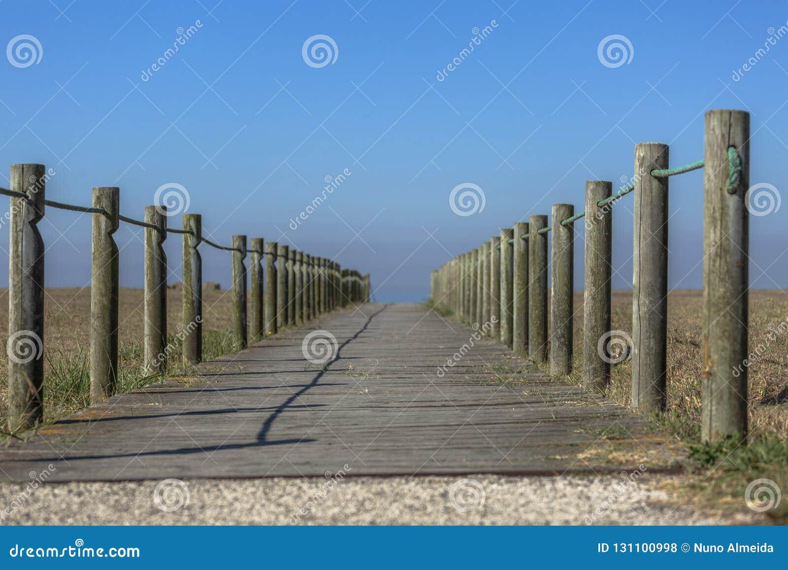 Perspectiefmening van houten voetgang, naar de oceaan, naast het strand