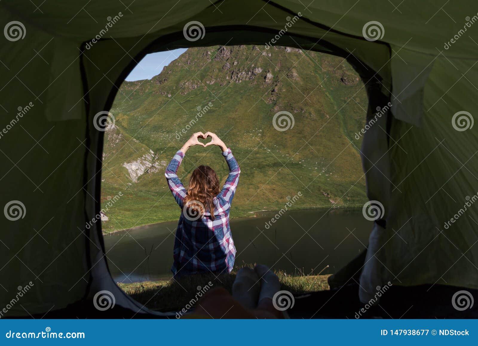 Perspectiva pessoal de um campista masculino na barraca nos cumes suíços com uma jovem mulher que faz a forma do coração da mão n