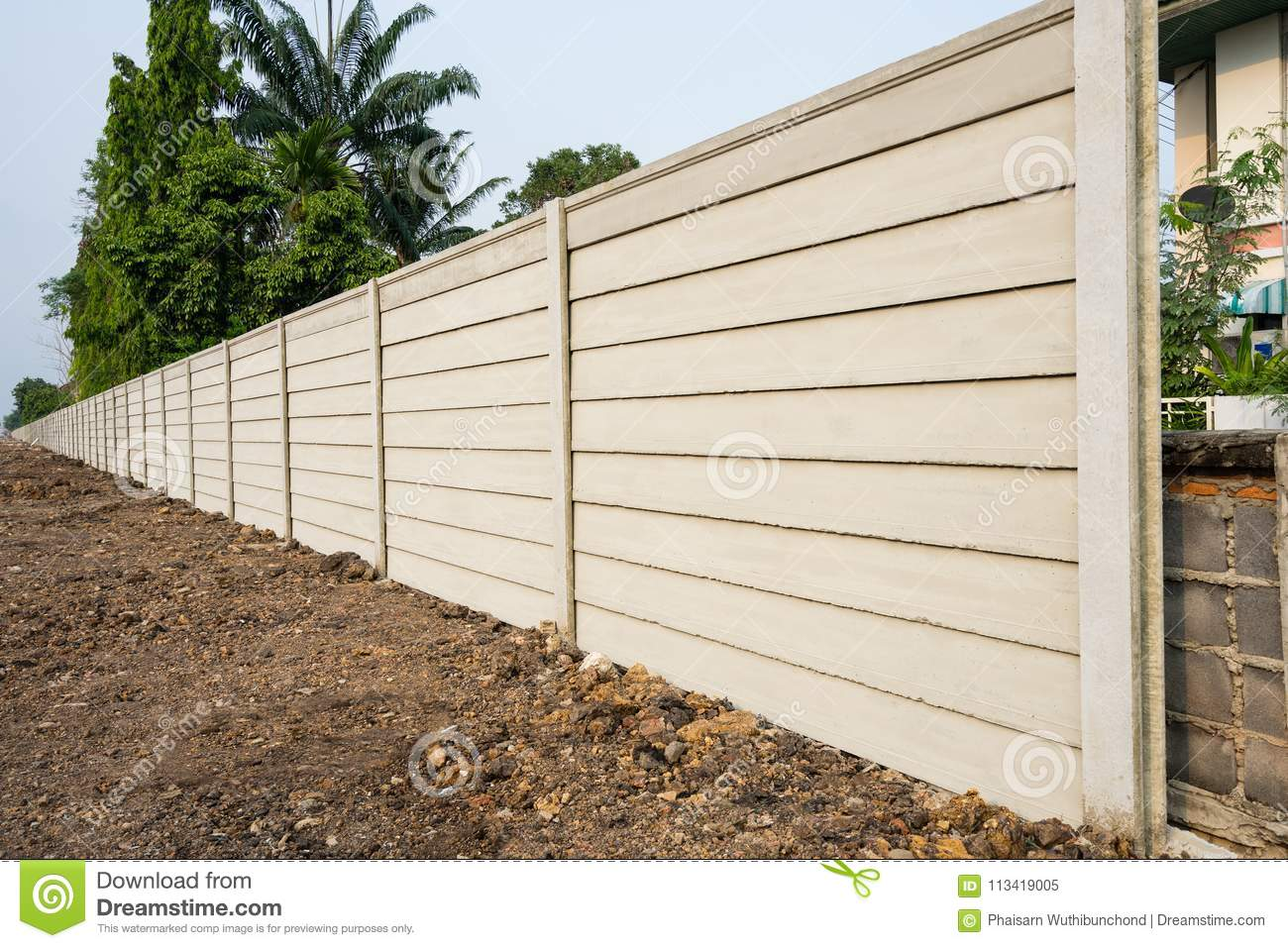 Perspective view of precast panel concrete wall on fresh ground floor, prefabricated cement compound wall over trees background