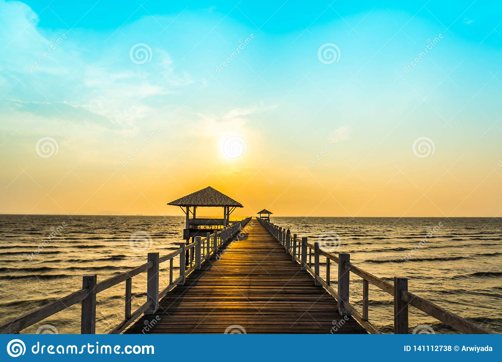 Perspective view of wooden bridge extending into the sea