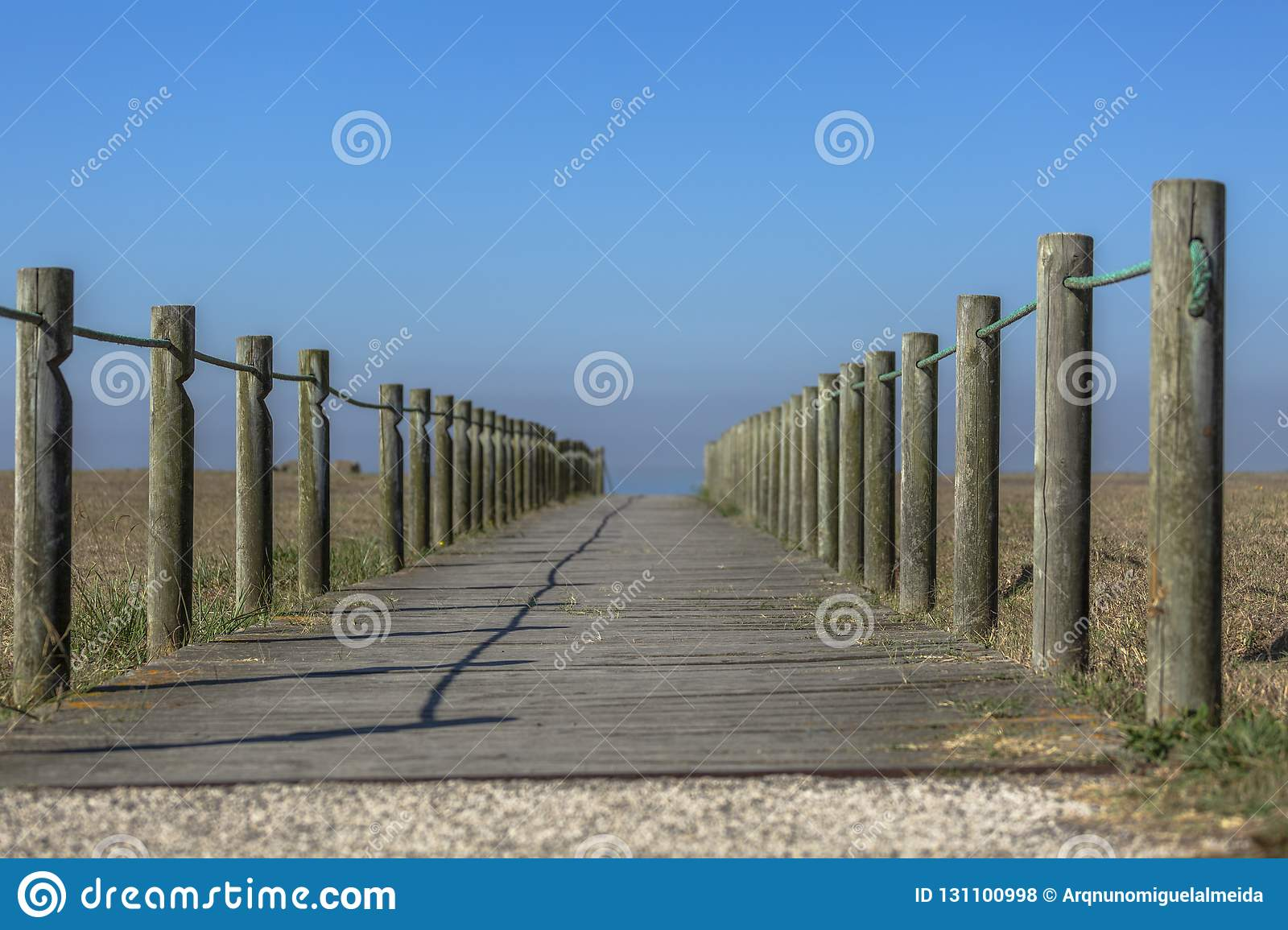 Perspective view of wooden pedestrian walkway, towards the ocean, next to the beach