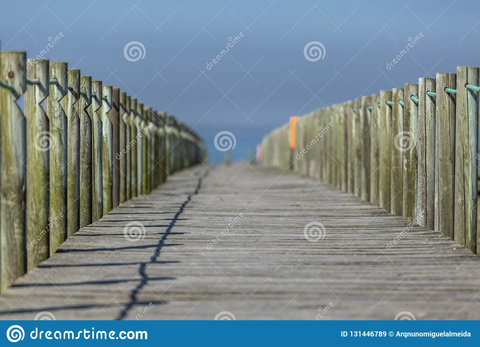 Perspective view of wooden pedestrian walkway, towards the ocean, next to the beach, Portugal