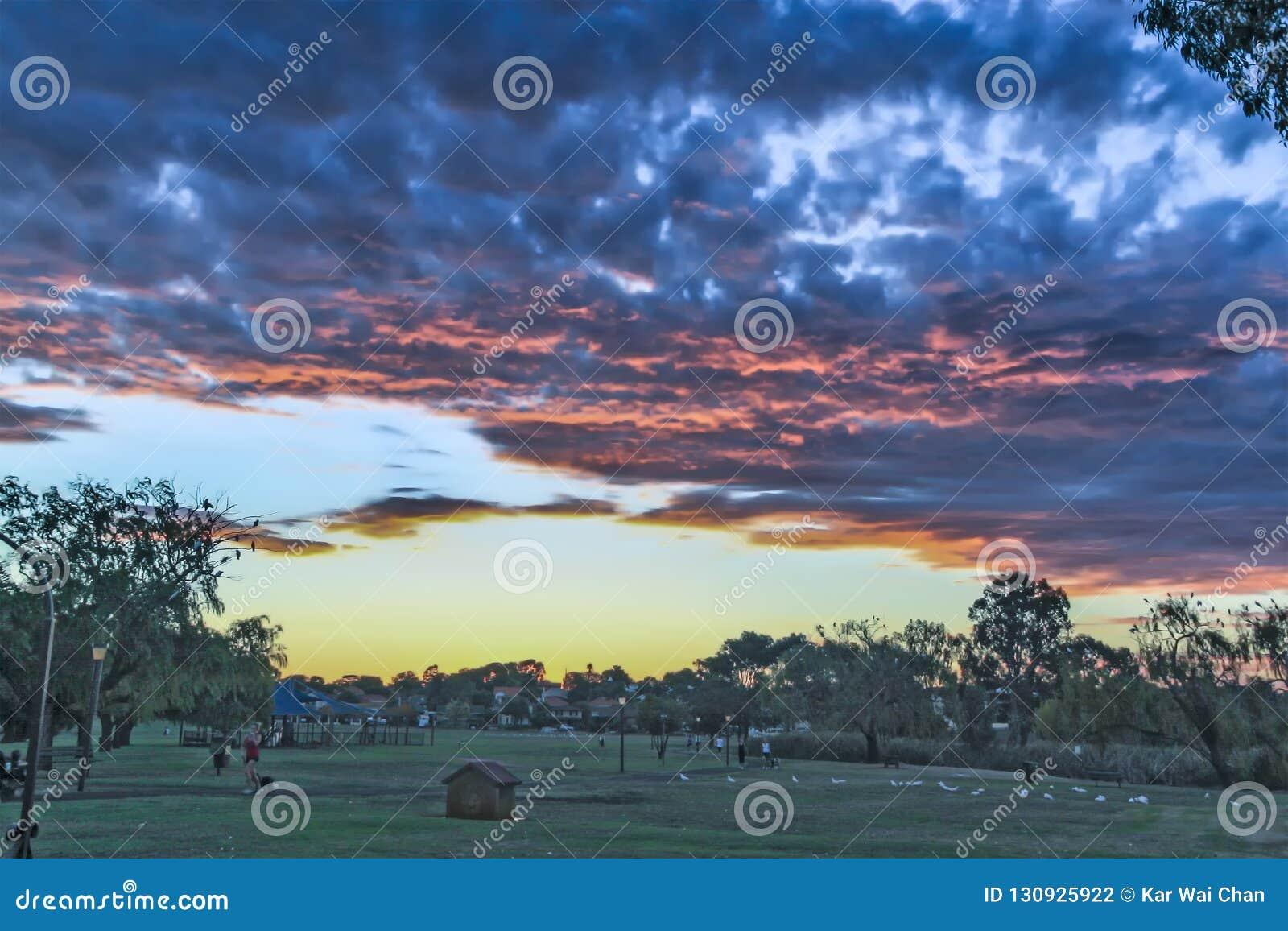 Perth - 2011: Por do sol em um parque com nuvens escuras
