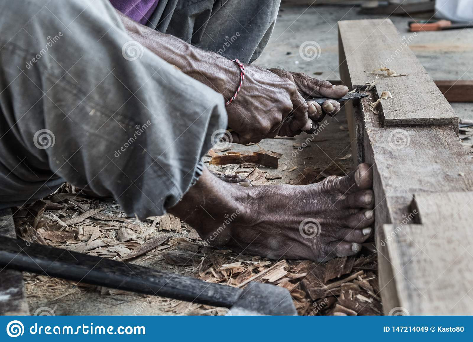 Perto acima de advirta as m?os do carpinteiro que trabalham na loja manual tradicional da carpintaria em um pa?s do terceiro mund