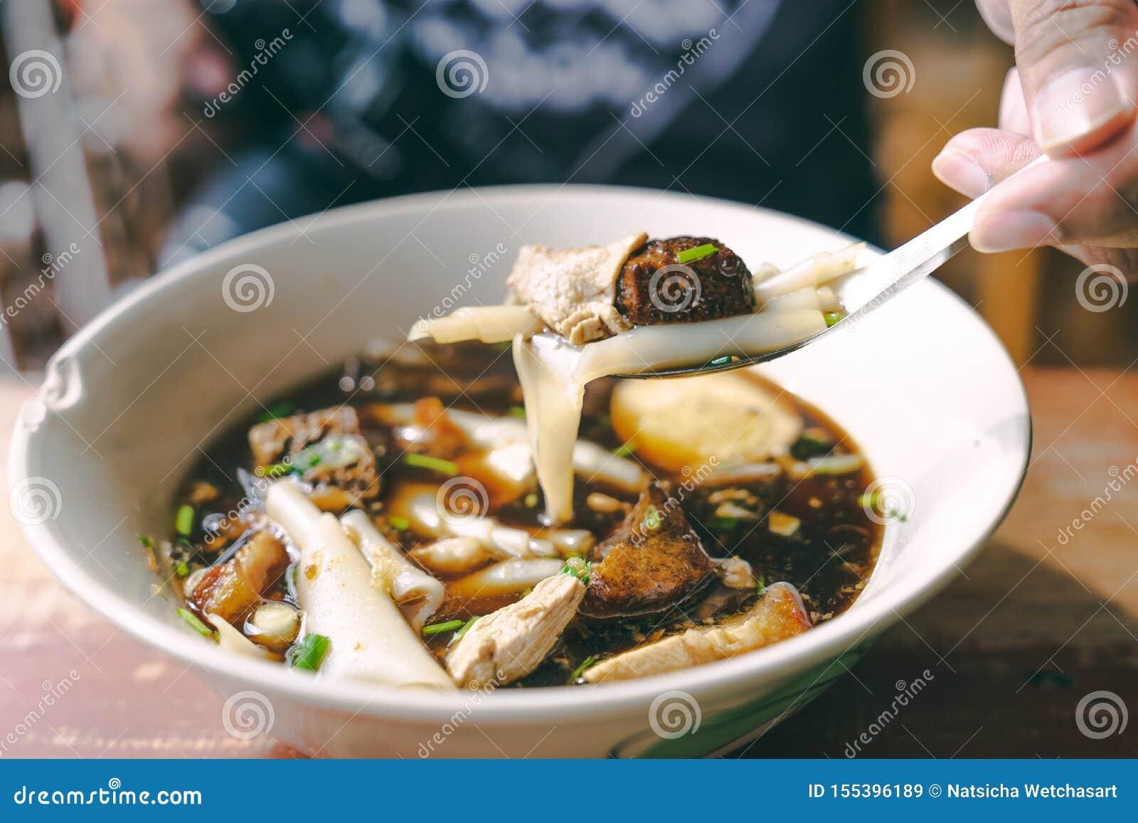 Perto acima do jub de Guay, do alimento tailandês da rua da sopa de macarronete do molho na tabela de madeira com mão e da forqui