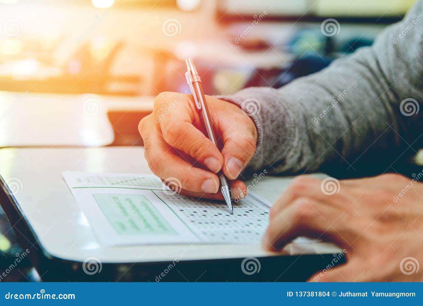 Perto acima, os exames do lápis da terra arrendada do estudante masculino de High School que escrevem na sala de aula para o test
