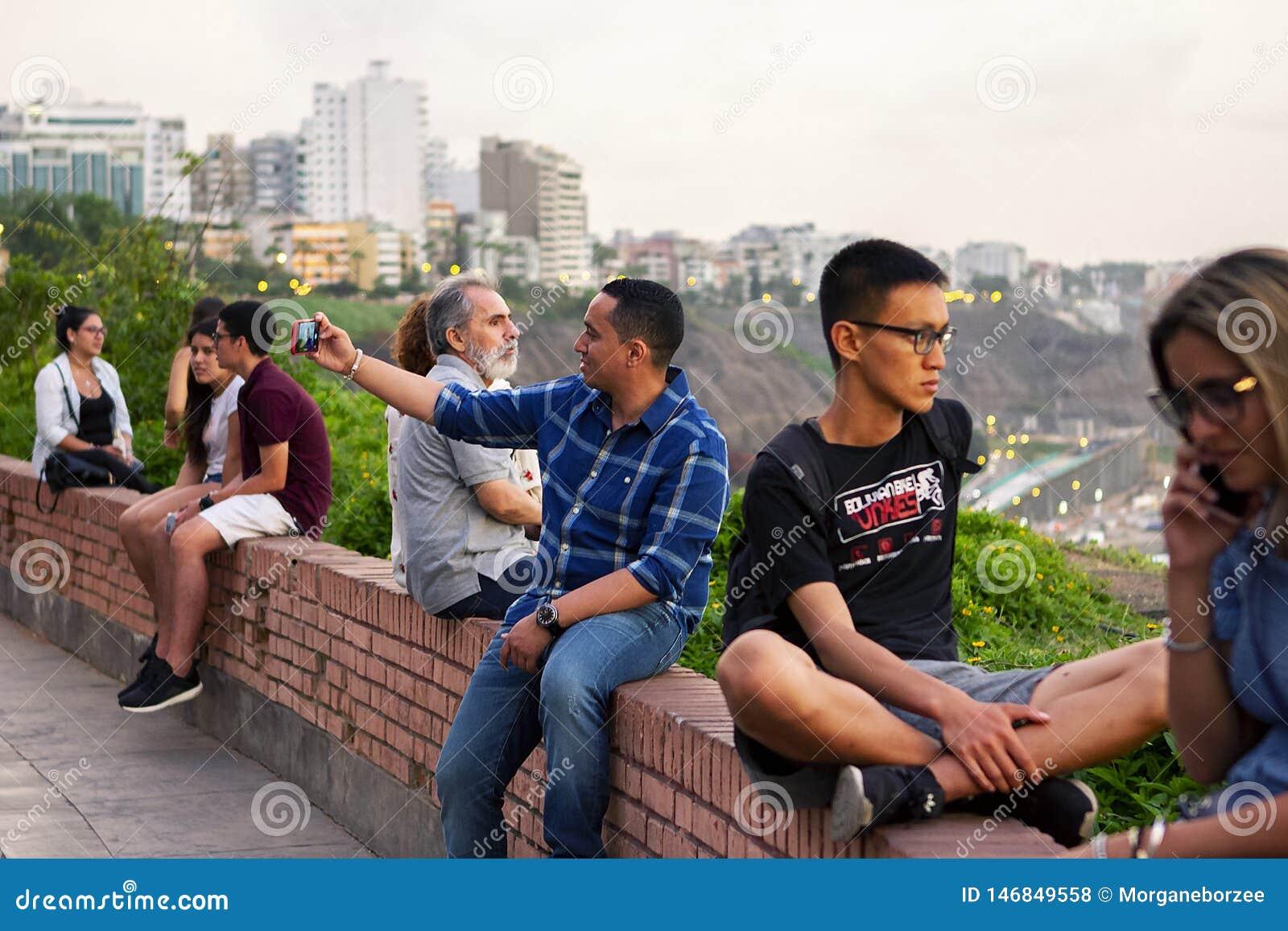 Peruanische Leute und Touristen, die den Sonnenuntergang aufpassen und selfies nehmen