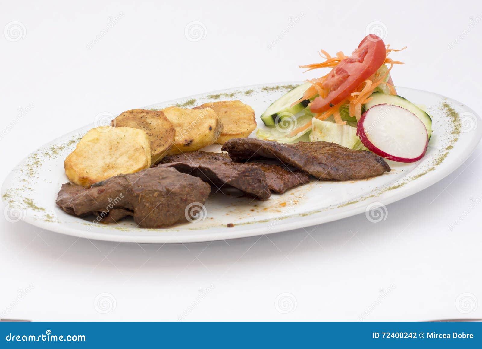 Peruansk maträtt: anticuchos, grillat skewered nötkötthjärtakött med den kokta potatisen och sallad