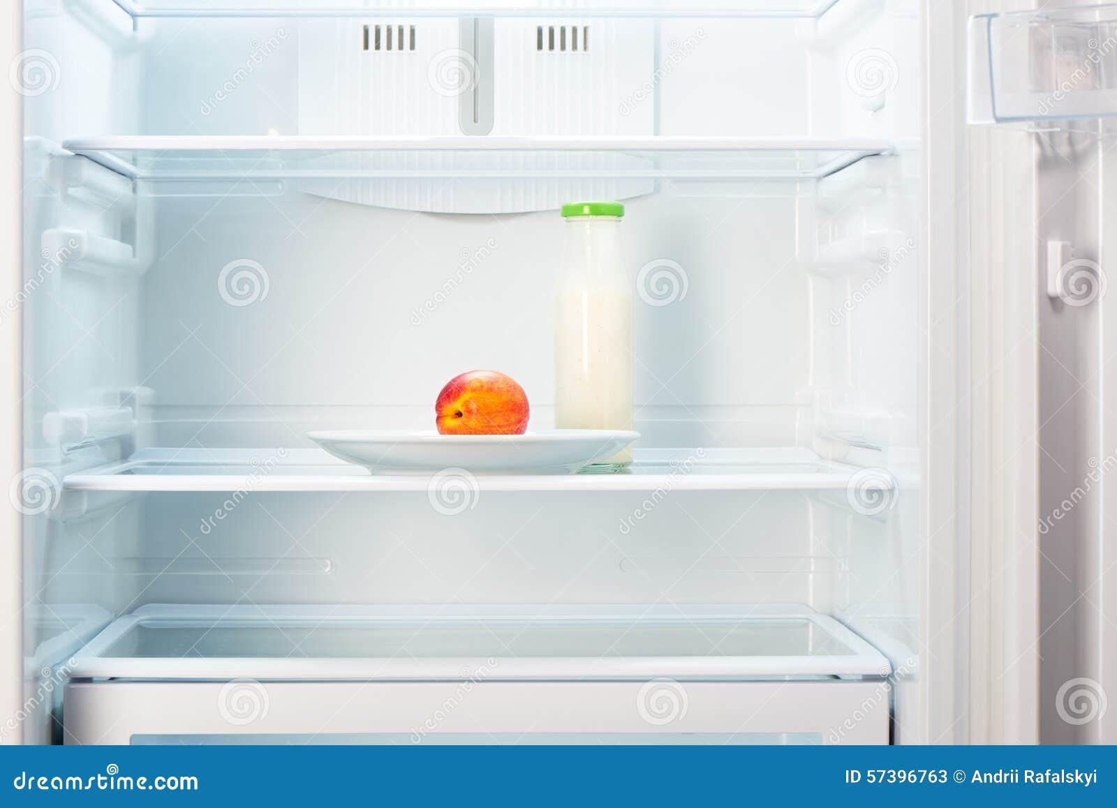 Perzik op witte plaat met fles yoghurt in ijskast