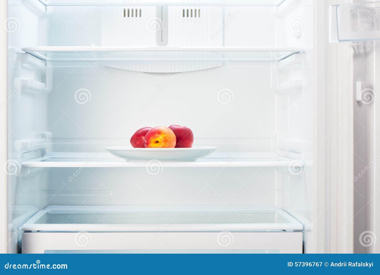 Perziken op witte plaat in open lege ijskast