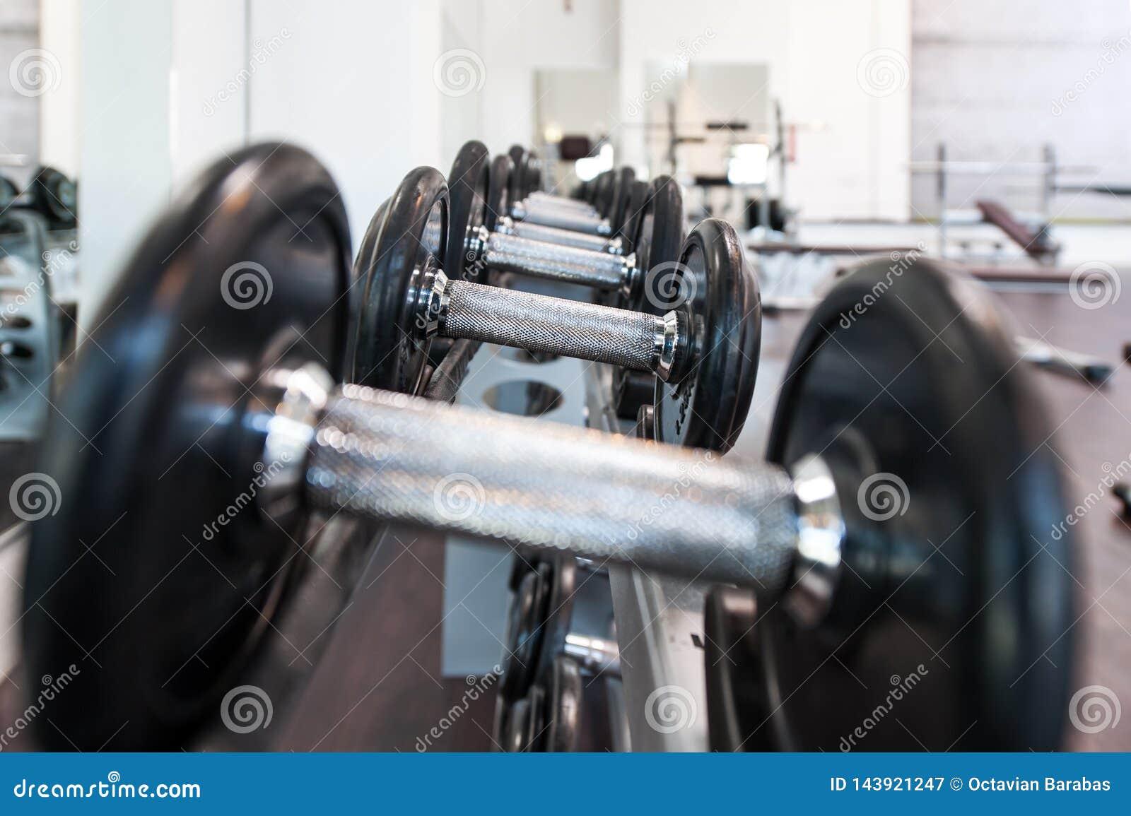 Pesas de gimnasia múltiples del hierro en centro de deporte