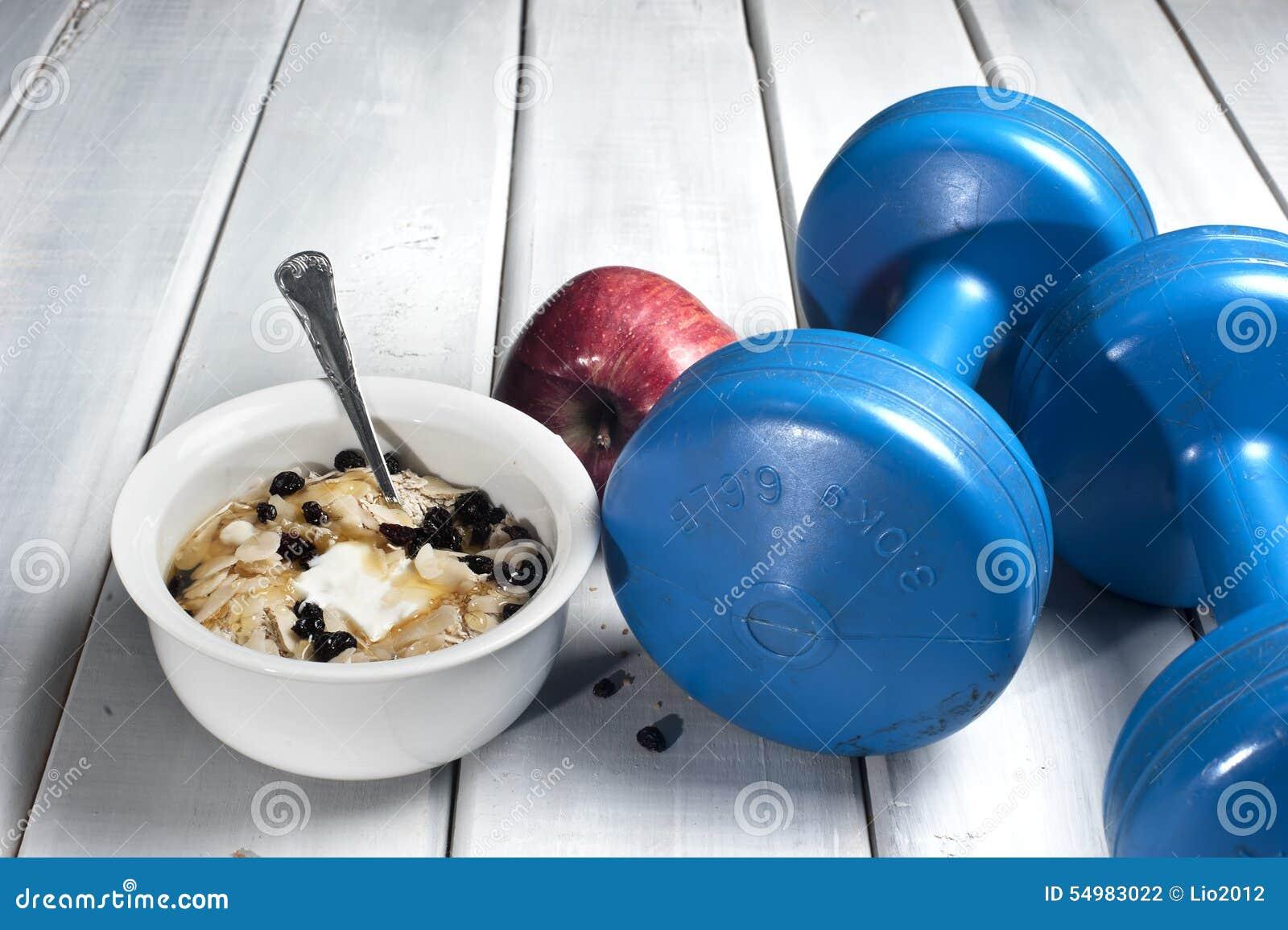 Pesas de gimnasia y cuenco con el yogur