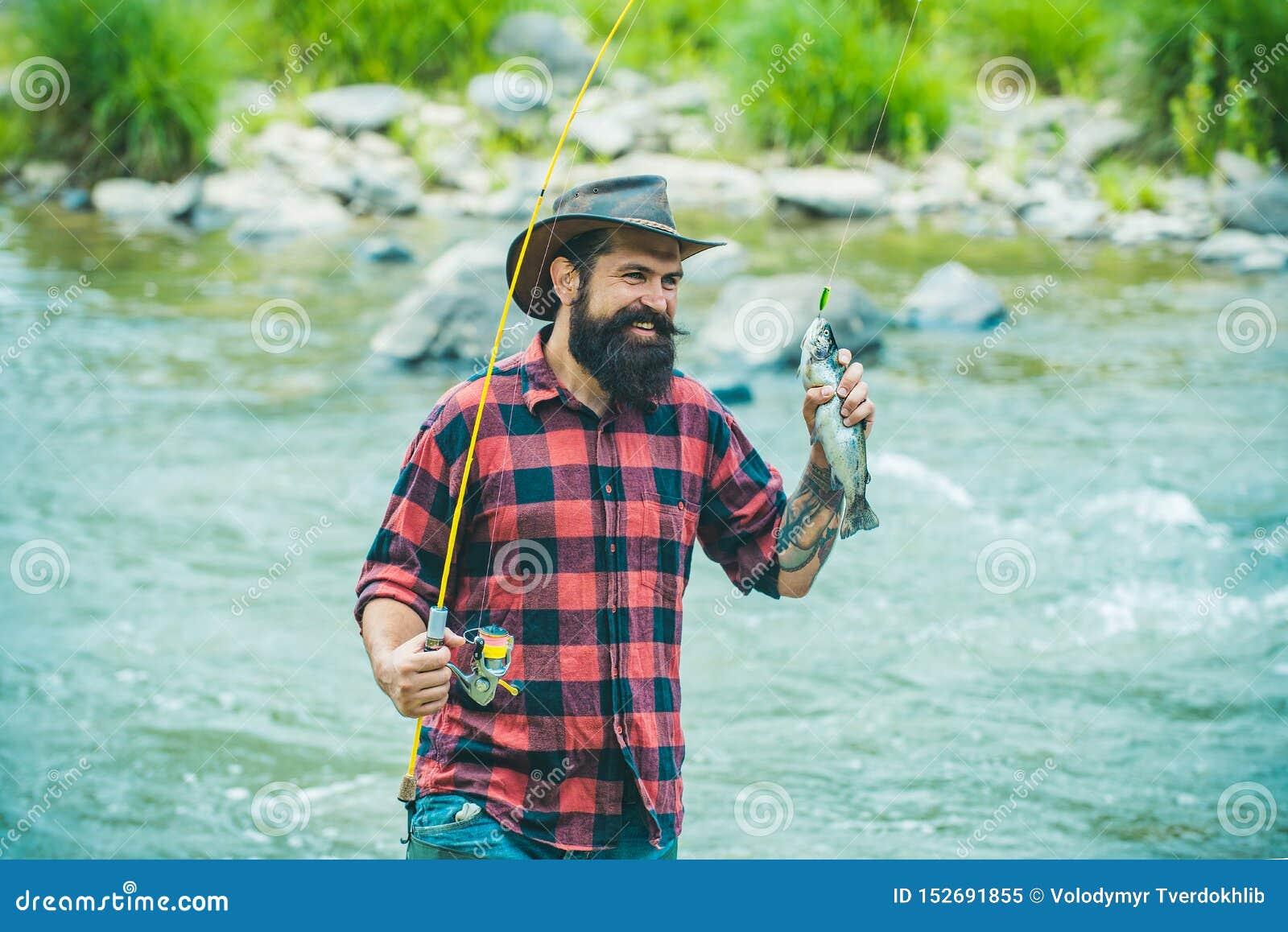 Pesca de la lubina Trucha del pescador y del trofeo Grayling del r?o en el gancho Pesca deportiva Método para coger la trucha Pes