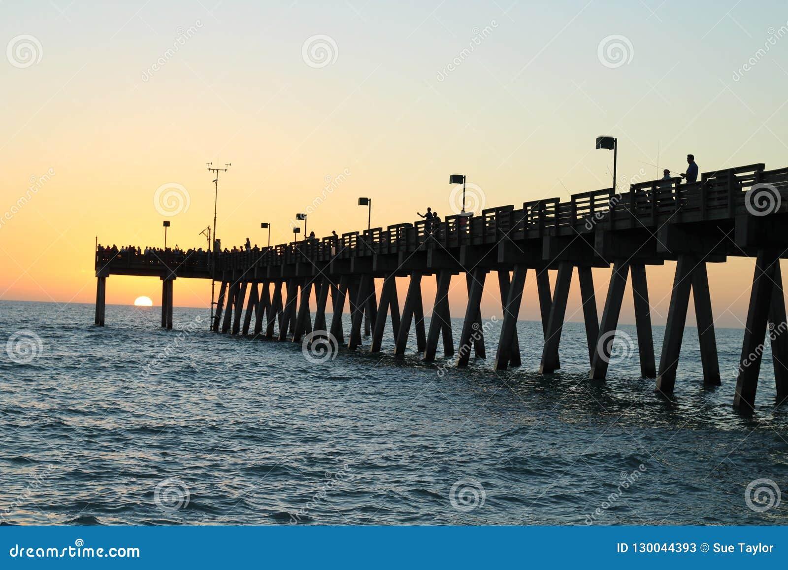 Pesca del embarcadero en el Golfo de México en la puesta del sol