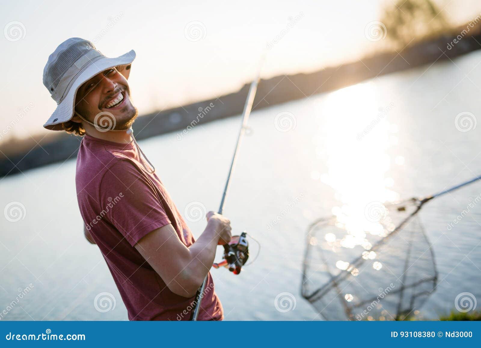 Pesca del giovane su un lago al tramonto ed all hobby godere