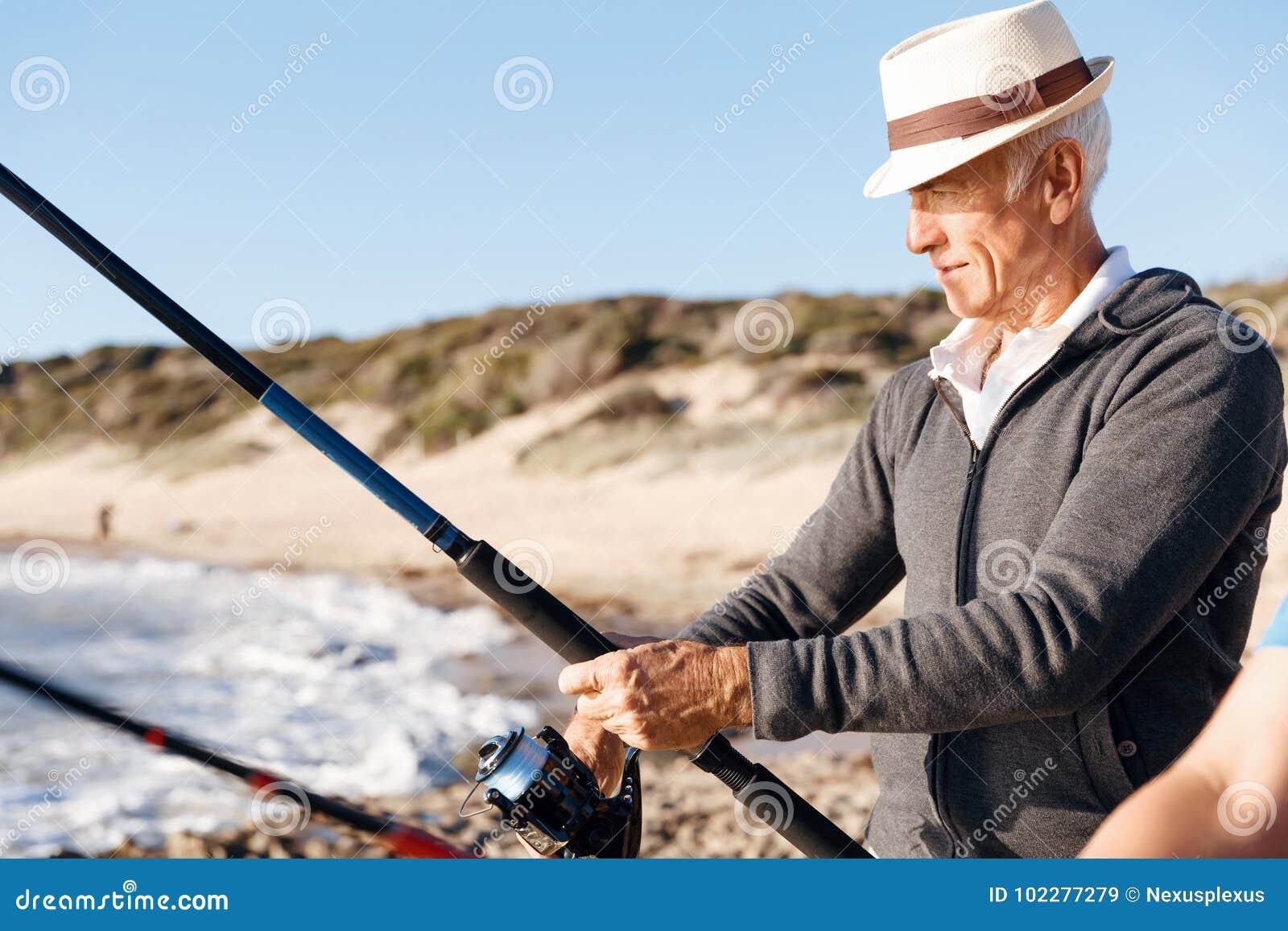 Pesca del hombre mayor en el lado de mar