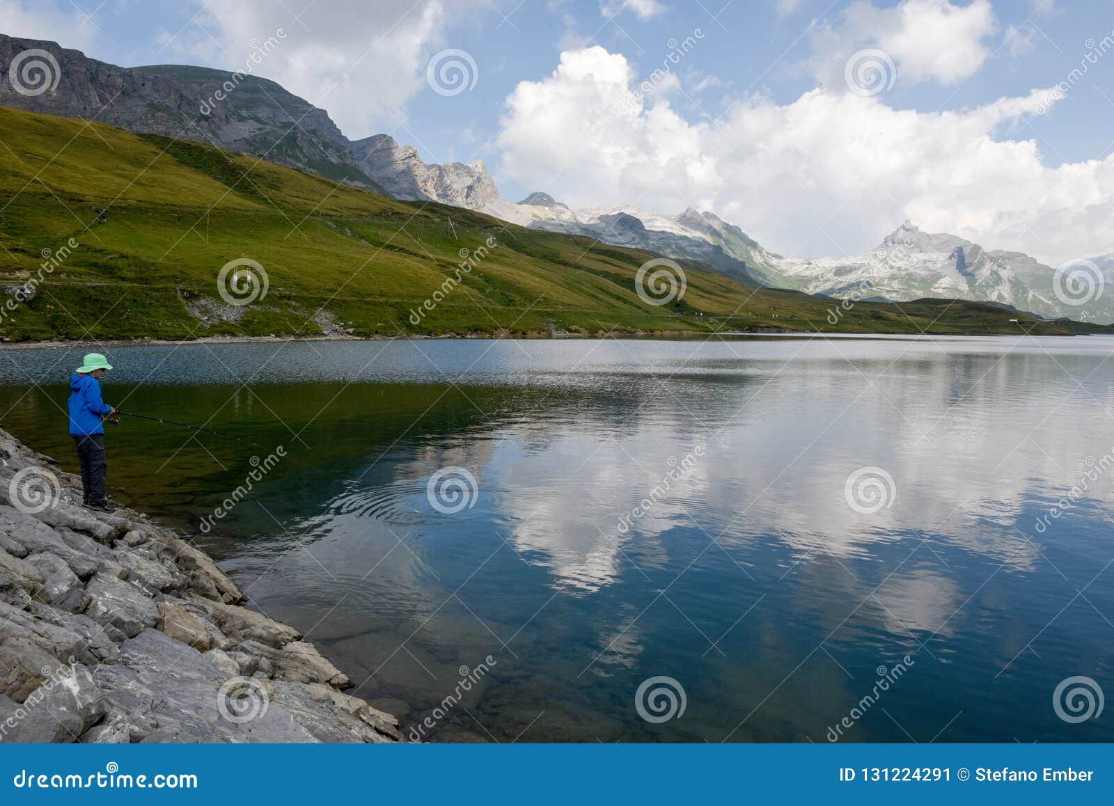 Pesca del muchacho en el lago Tannensee en las montañas suizas