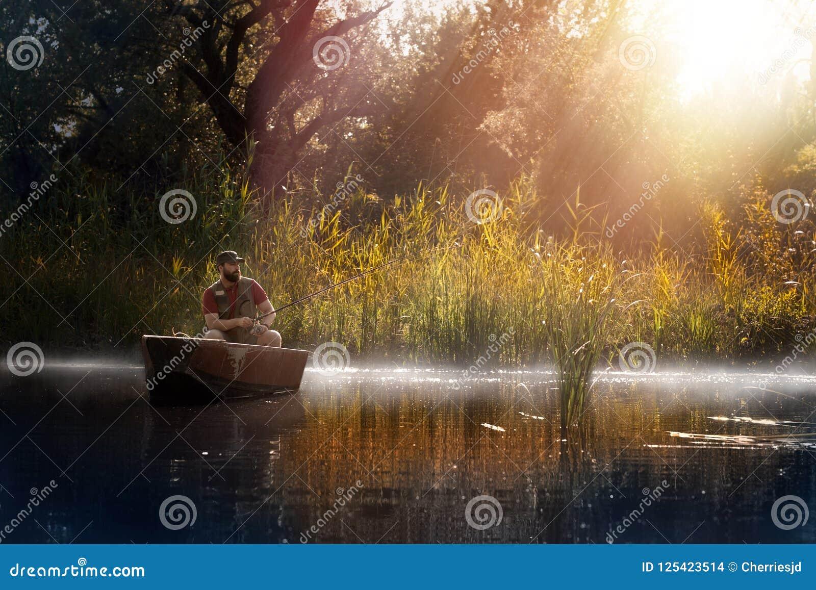 Pesca Pesca dell uomo su un lago sulla barca