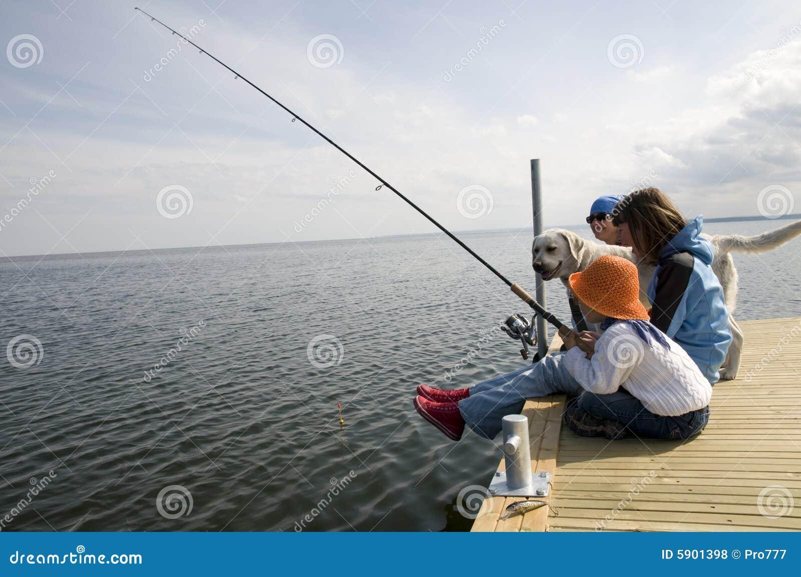 Pesca della famiglia con il cane