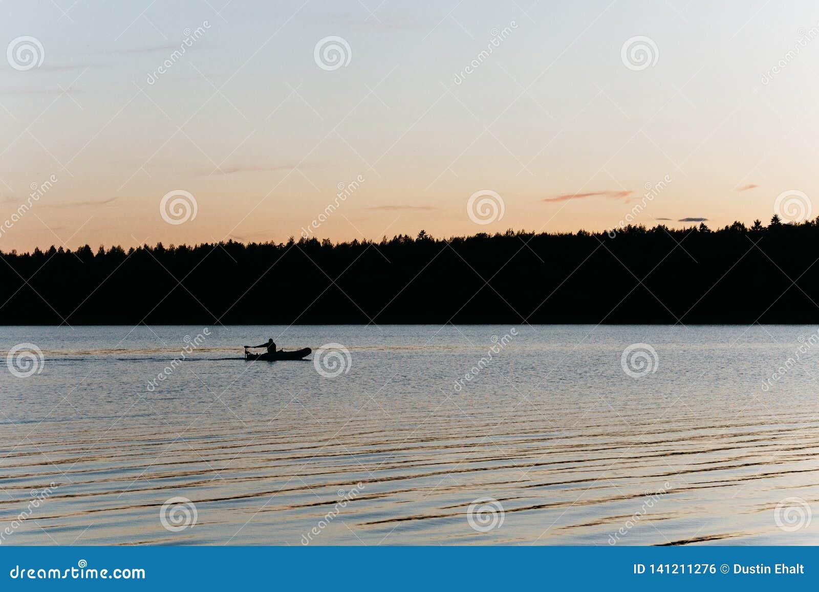Pesca della siluetta su un piccolo lago