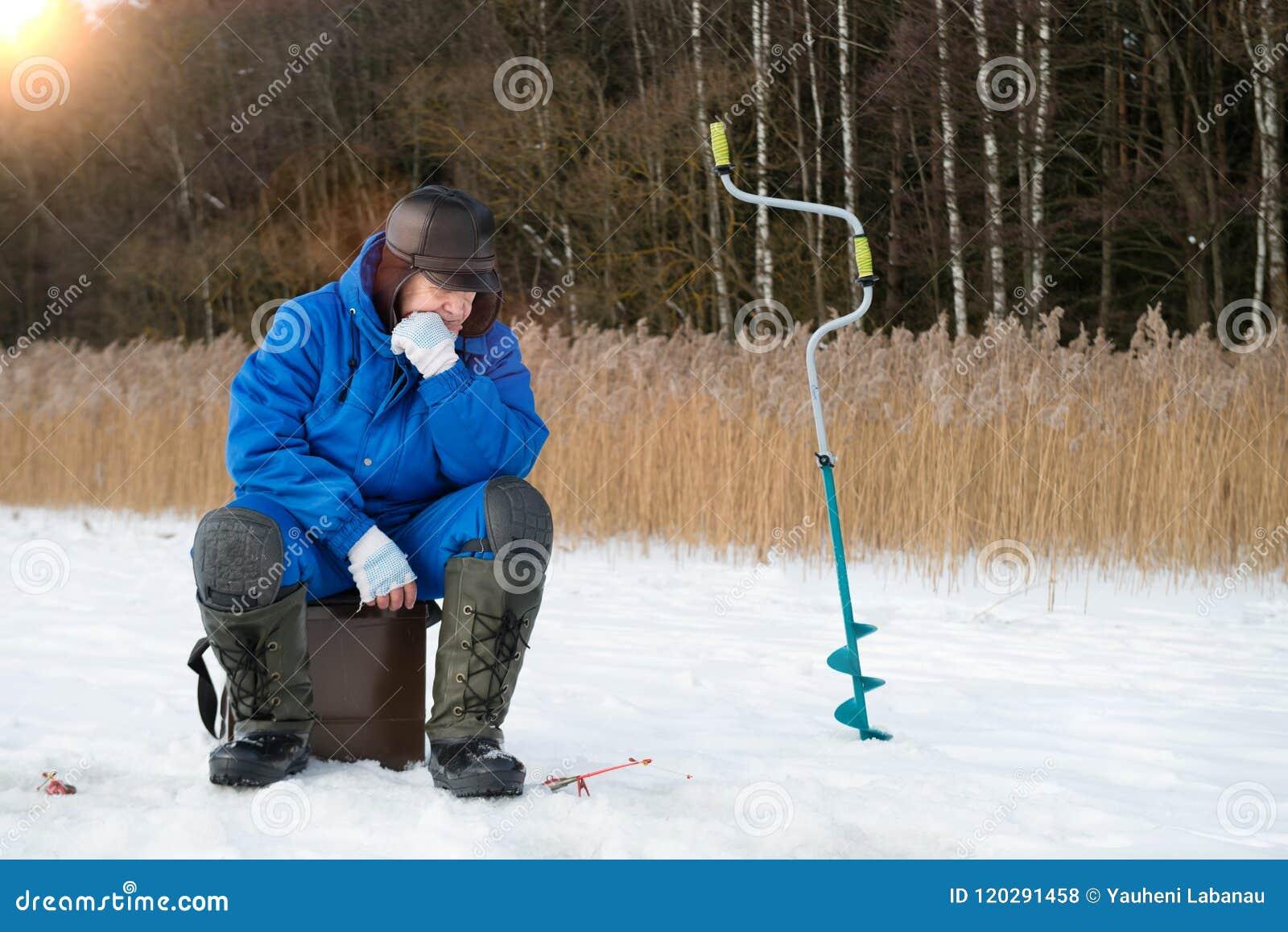Pesca di inverno Il fermo aspettante dell uomo al giorno di freddo di inverno