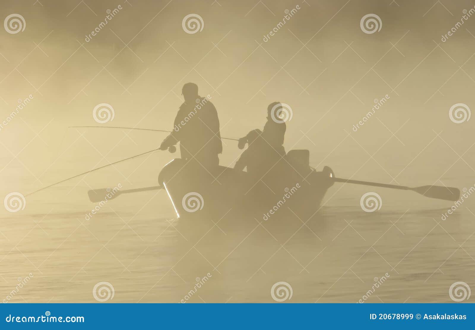Pesca di mosca in una barca di direzione nella nebbia