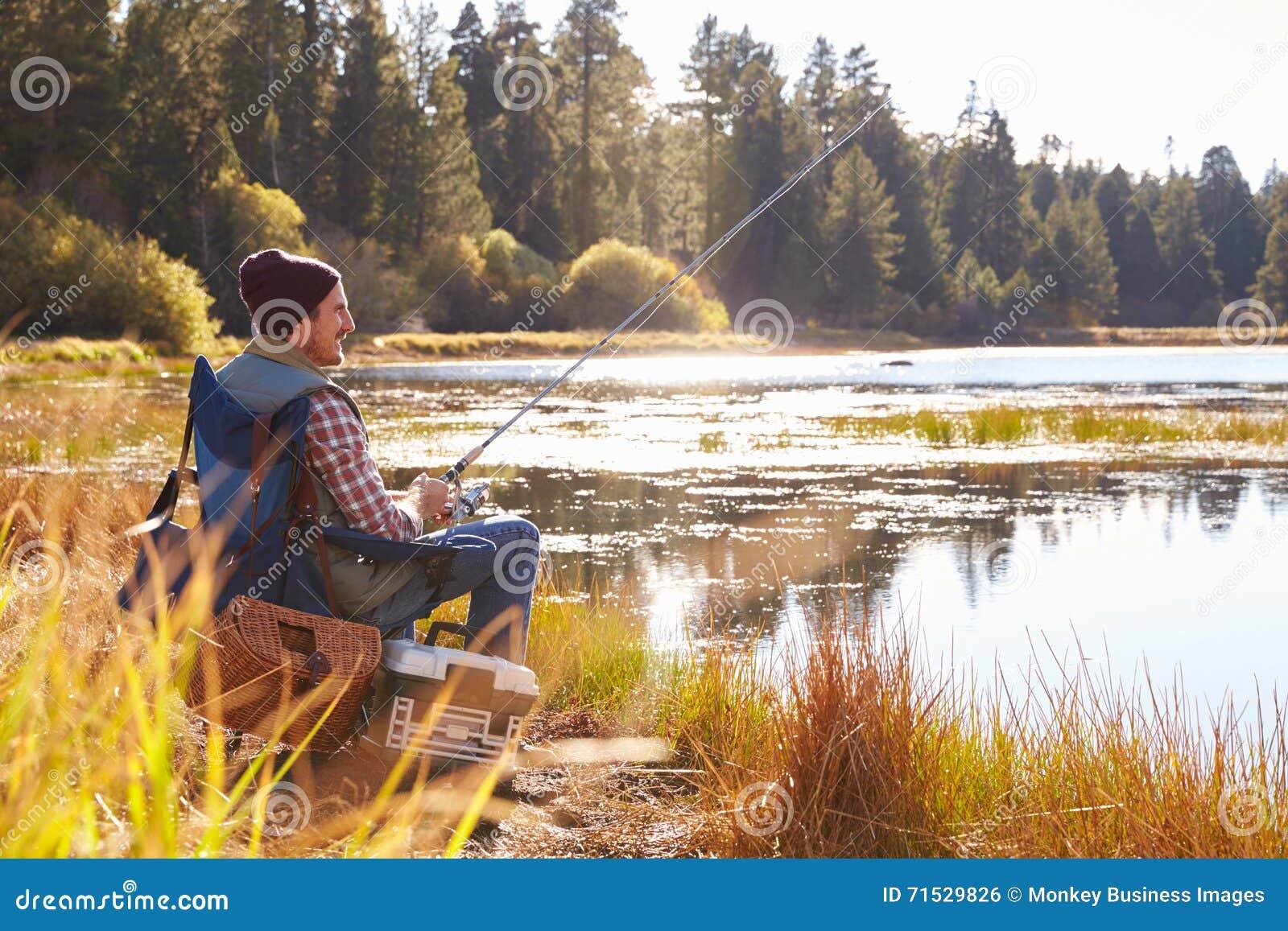Pesca do homem do Meados de-adulto pela beira do lago, Big Bear, Califórnia, EUA