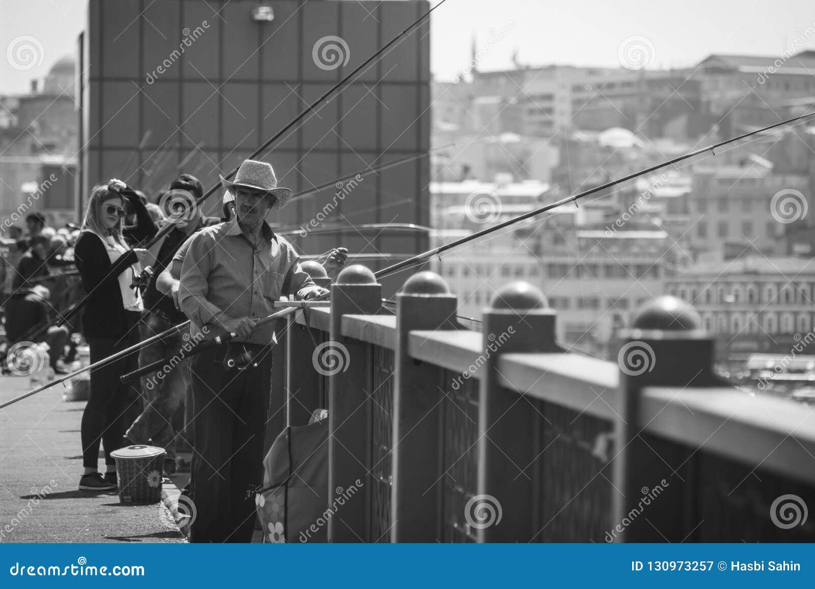 Pesca e turistas do homem que visitam na ponte de Galata