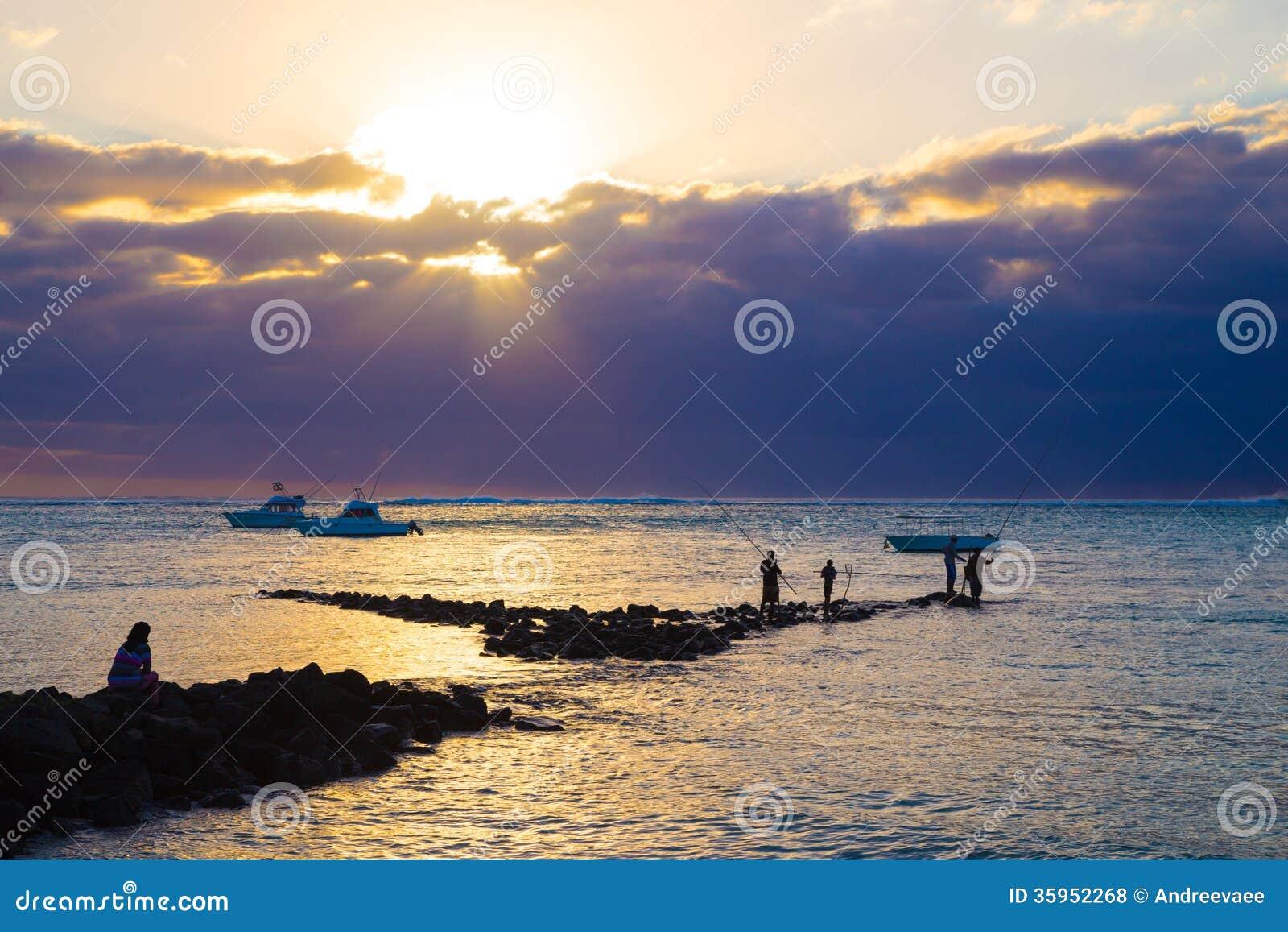 Pesca en mar en la puesta del sol