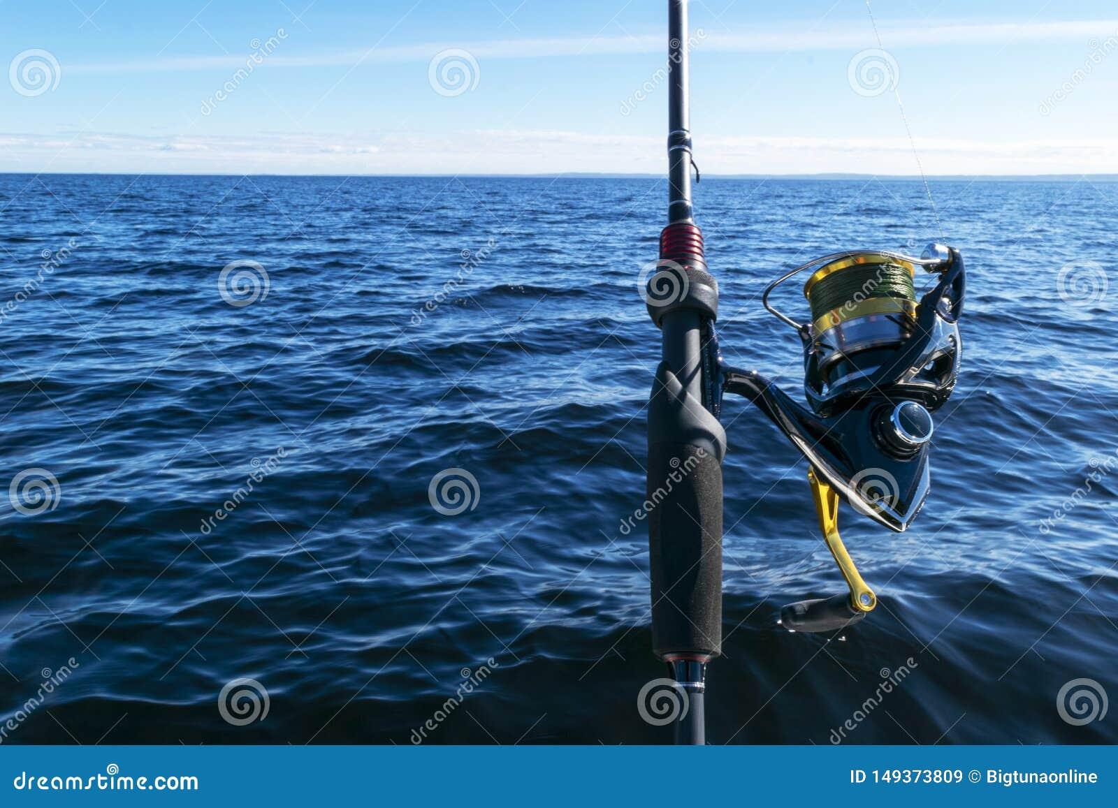Pesca no lago M?os do pescador com vara de pesca Tiro macro A vara de pesca e as m?os do pescador sobre o lago molham girar