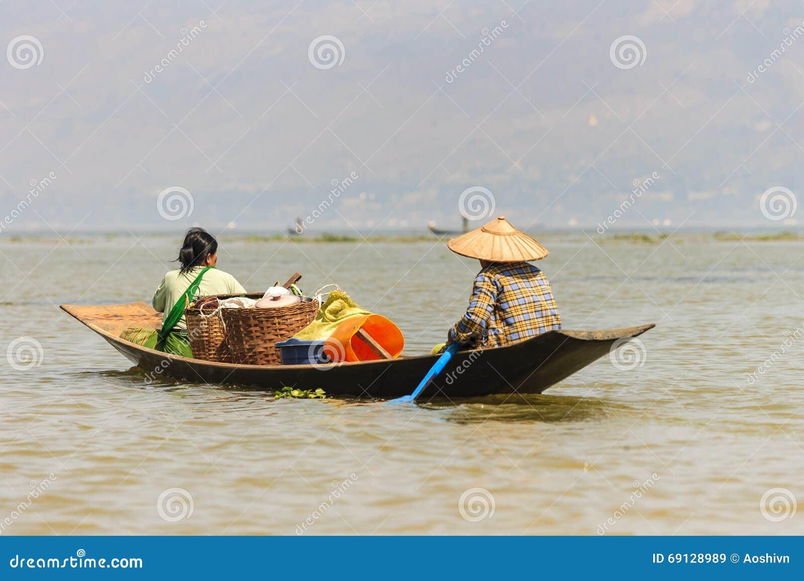 Pescador burmese não identificado em peixes de travamento do barco de bambu na maneira tradicional com rede feito a mão